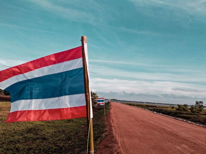 Thai flag on land against sky