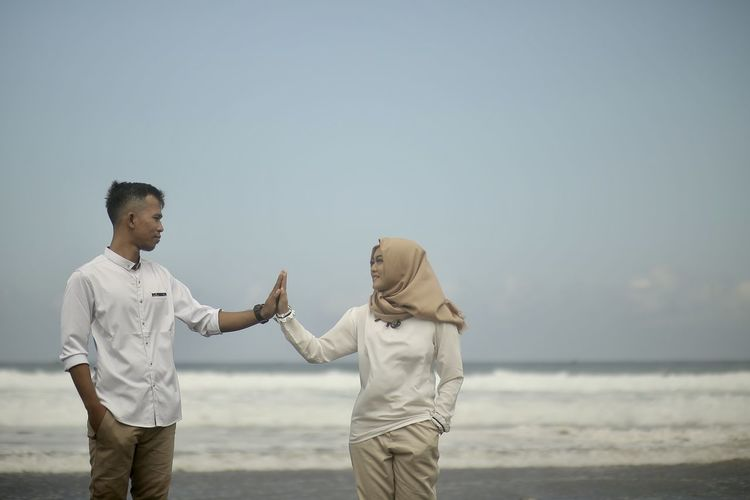 Full length of couple standing on beach against clear sky