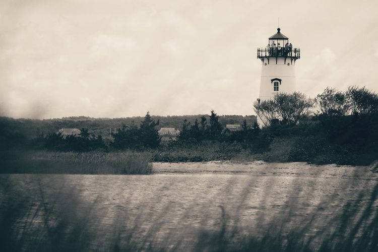 Lighthouse amidst trees and buildings against sky