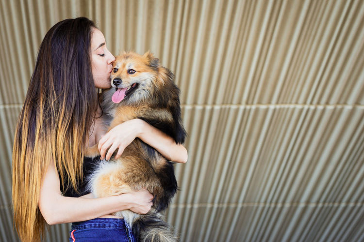 Woman kissing dog outdoors