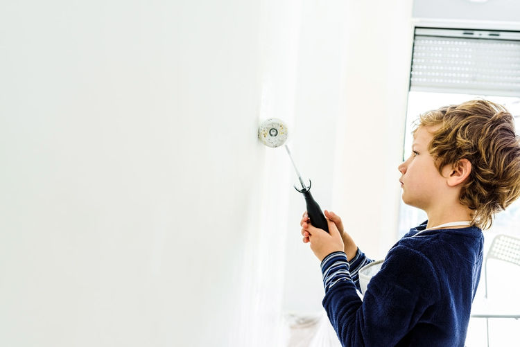Portrait of boy holding wall at home