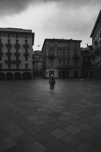 Rear view of girl walking on empty street amidst buildings in isolated city during covid-19.