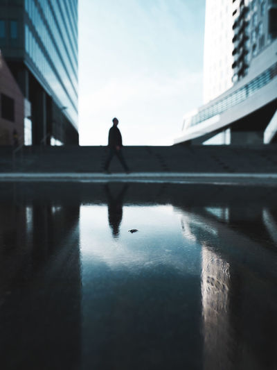 Reflection of silhouette person walking on footpath by swimming pool in city against sky