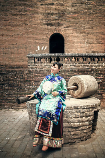 Smiling Young Woman With Hand Fan Sitting Outside Historic Building
