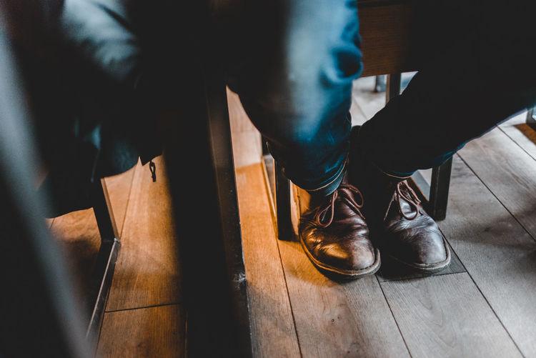 Low section of man sitting on hardwood floor