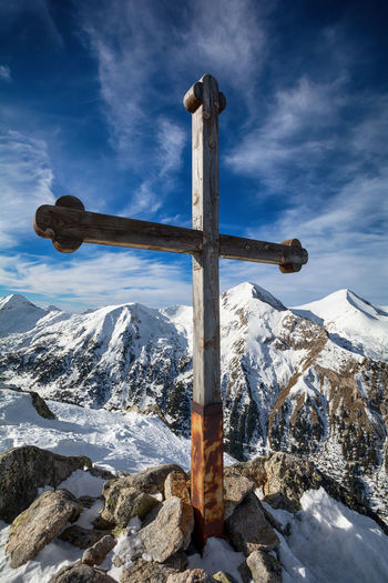 Cross on snow covered mountain against sky