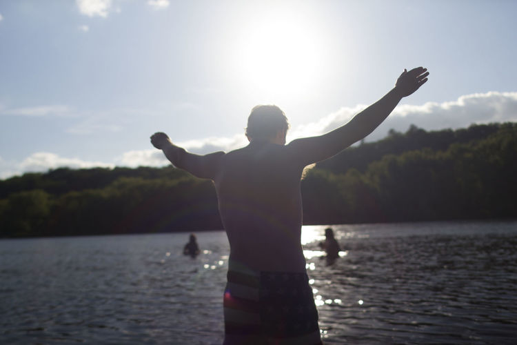Adult Arms Outstretched Beauty In Nature Day Human Hand Lake Leisure Activity Lifestyles Men Nature One Person Outdoors People Real People Rear View Scenics Shirtless Sky Standing Sunlight Sunset Tree Victory Water