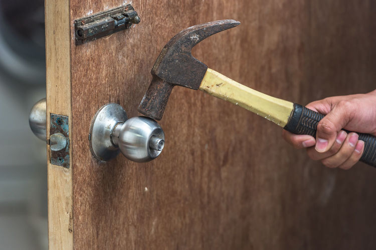 Cropped Hand Of Man Breaking Doorknob With Hammer