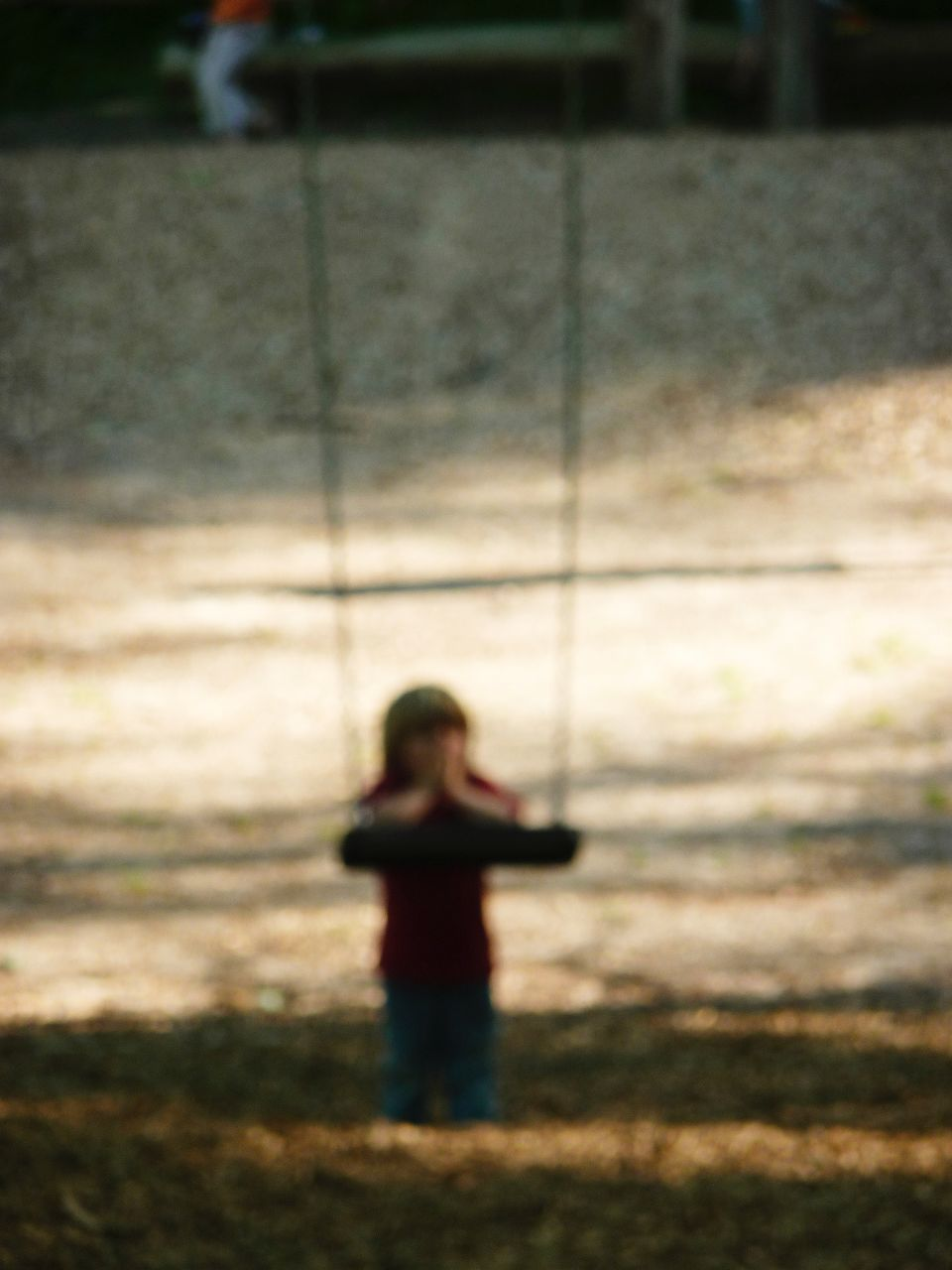 Defocused Image Of Child By Swing At Park