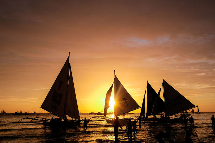 Holiday Philippines Relaxing Beauty In Nature Boracay Cloud - Sky Horizon Horizon Over Water Leisure Activity Men Mode Of Transportation Nature Nautical Vessel Orange Color Outdoors Real People Sailboat Scenics - Nature Sea Silhouette Sky Sunset Transportation Water Waterfront