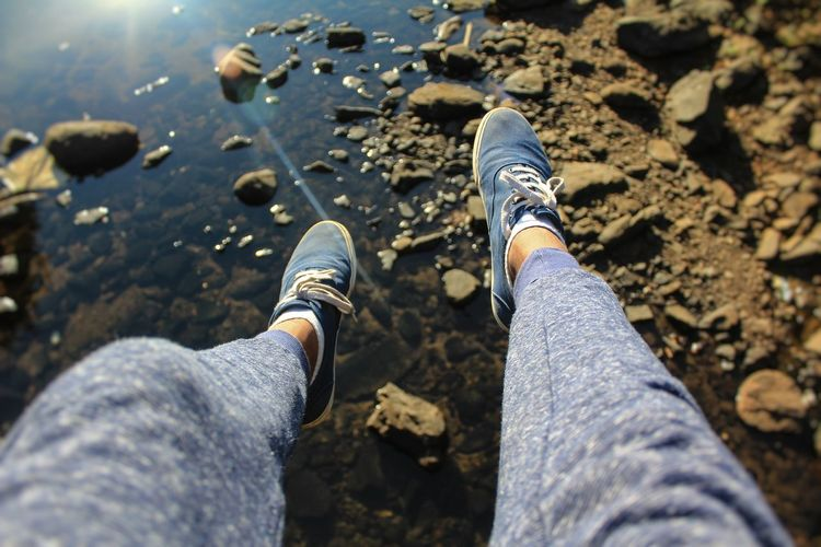 Low Section Of Man Wearing Shoes Over Lake