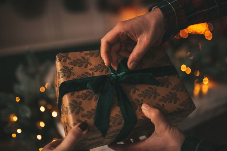 Cropped hand of man and woman opening christmas gift