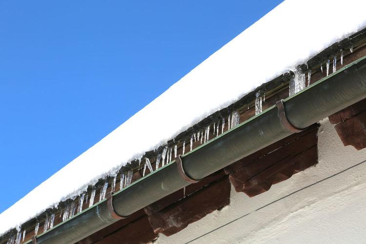 Snow on railroad tracks against clear blue sky
