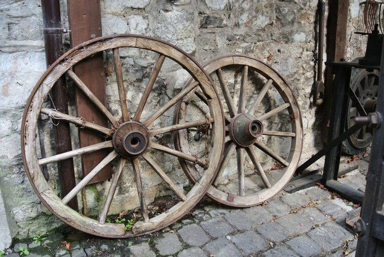 Wagon Wheels On Footpath Against Wall