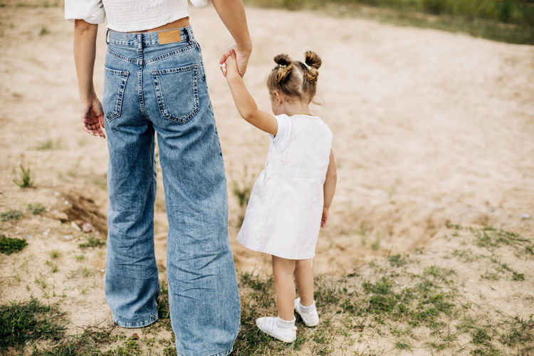 Mom and her little daughter are walking, holding hands, spending time together