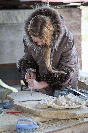 Young woman working on stone