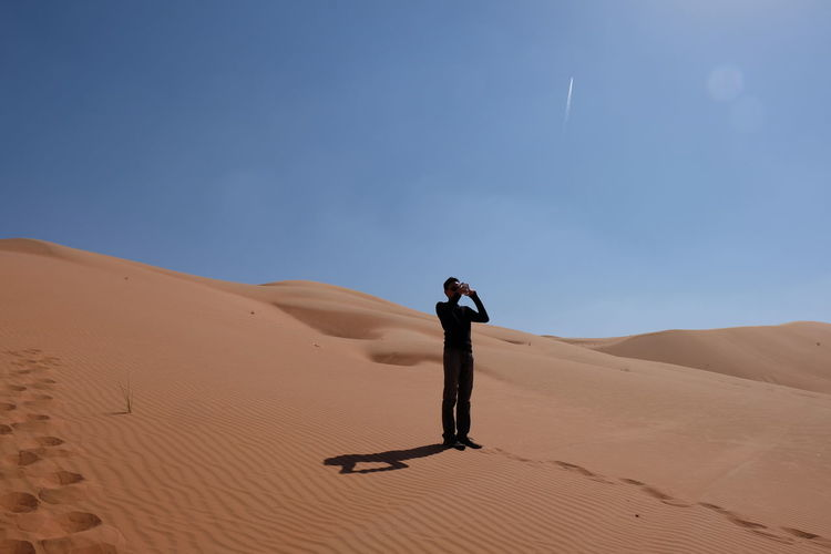 Man photographing while standing on sand against clear sky