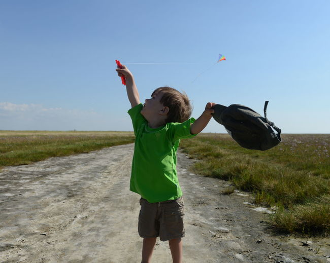 Boy flying kite while standing on road amidst grassy field against sky during sunny day