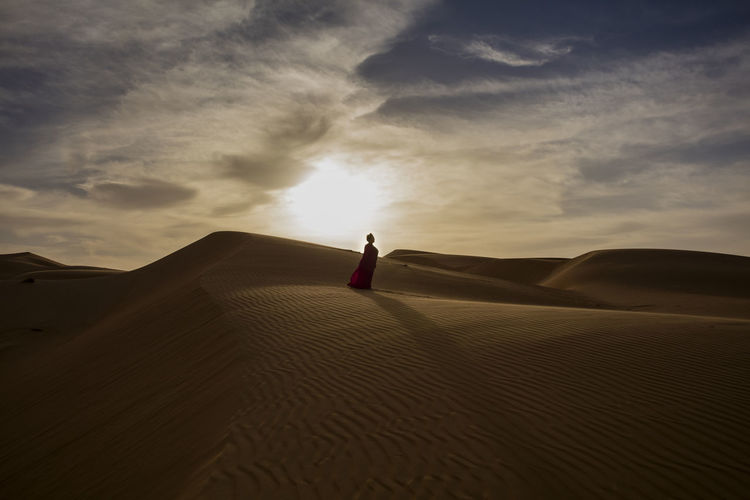 Woman standing on sand dune at desert against sky