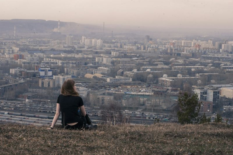 Rear view of woman looking at cityscape while relaxing on grassy hill