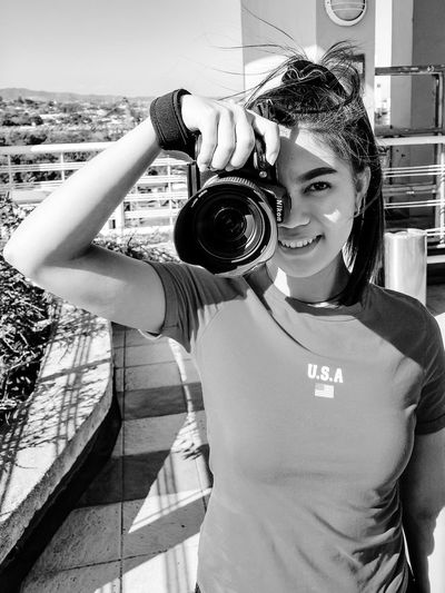 Portrait of teenage girl holding camera