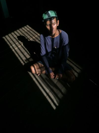 High angle view of man sitting in darkroom