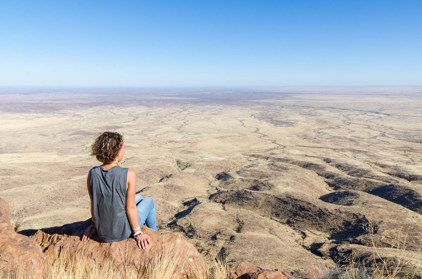 Adult Adults Only Arid Climate Barren Clear Sky Day Desert Horizon Over Land Landscape Looking At View Nature One Person One Woman Only Only Women Outdoors People Relaxation Remote Sand Sand Dune Scenics Sitting Solitude Tranquil Scene Tranquility