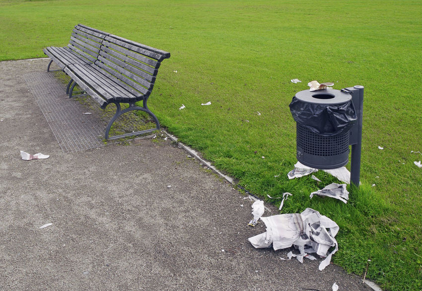 bench and litter outside rubbish bin in a public park Bench Neglected Rubbish Bin Day Dirty Garbage Grass Lawn Litter Negligence No People Outdoors Park Public Places Seat Untidy Waste