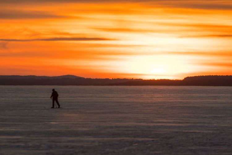 Sky Ski Skiing Scenics - Nature Beauty In Nature Tranquility Tranquil Scene Nature Canada Coast To Coast Orange Color Orange Orange Sky Sunset Silhouette One Person Full Length Real People Water Lifestyles Land Leisure Activity Winter Cold Temperature Outdoors