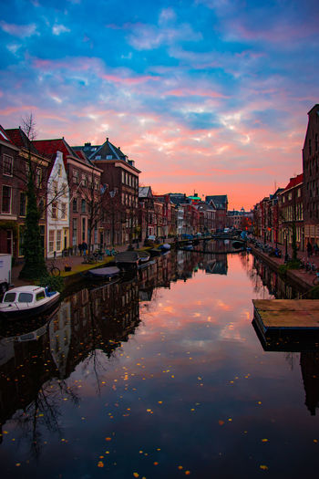 Boats moored in canal by buildings against sky during sunset