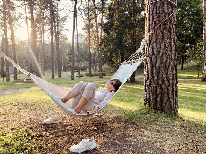 Man sitting on hammock in park