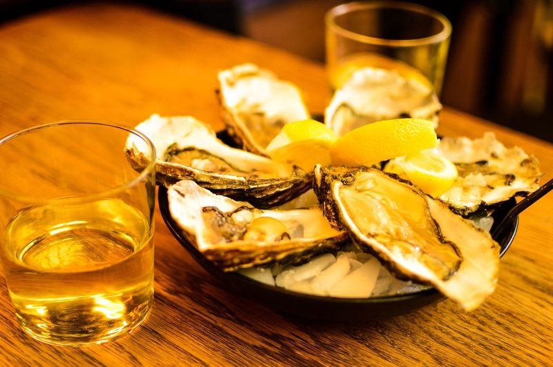 High Angle View Of Oysters With Whiskey Served On Table
