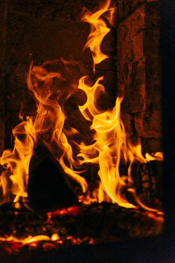 Close-up of fireplace with burning logs of wood. Fire Burning Fire - Natural Phenomenon Heat - Temperature Flame Glowing Night Motion Orange Color Nature No People Close-up Wood Log Firewood Wood - Material Event Long Exposure Fireplace Yellow Bonfire