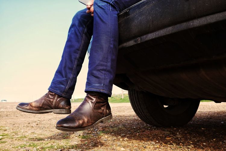 Low Section Of Man Sitting On Car