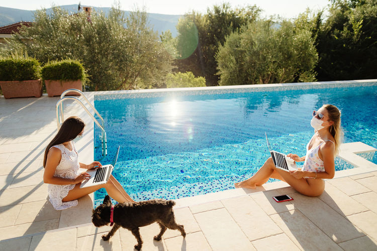 Women sitting by swimming pool against trees