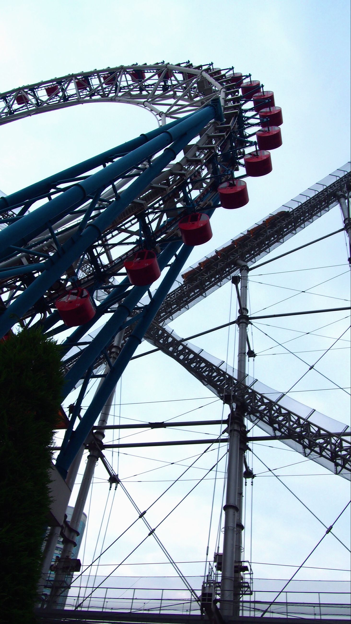low angle view, sky, clear sky, connection, amusement park, amusement park ride, metal, day, cable, arts culture and entertainment, outdoors, no people, electricity pylon, built structure, ferris wheel, power line, metallic, engineering, blue, nature