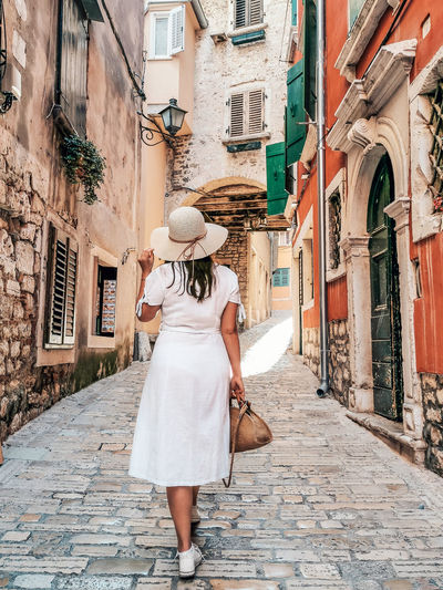 Young woman in white dress walking in old town street.