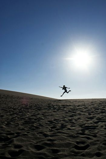 Silhouette Of Person Jumping In Desert