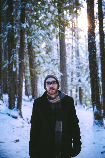 Portrait of man standing in forest during winter