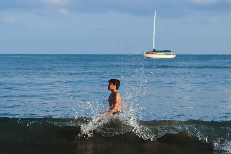 Boy looking away while standing in sea