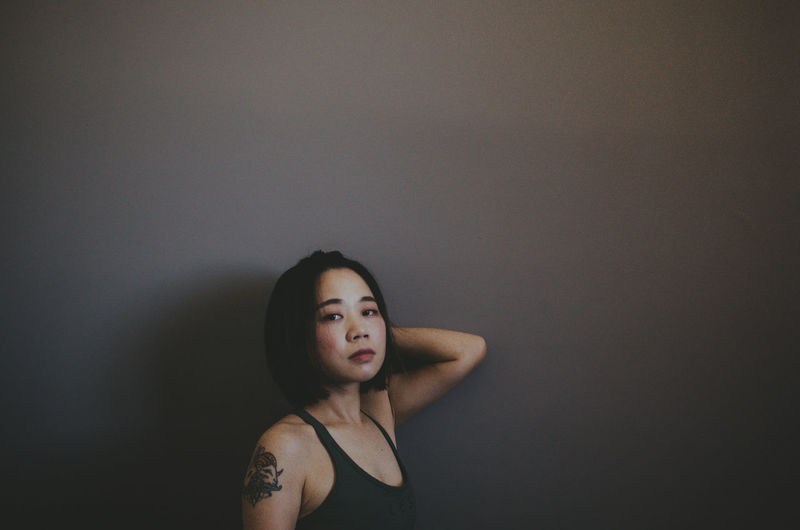 Portrait of woman against gray wall