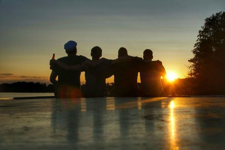 Silhouette men against sky during sunset