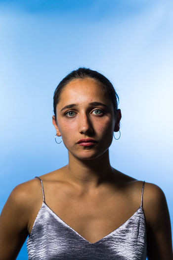 Studio shot of a young woman on mixed race ethnicity. Young Woman Mixed Race Person Indian Medium Shot Studio Shot Tanned Tank Top Beautiful Woman Portrait Front View Blue Background One Person Young Adult Natural Beauty Indoors  Studio Lighting Looking At Camera Colored Background Serious Blue Beauty Sleeveless Top