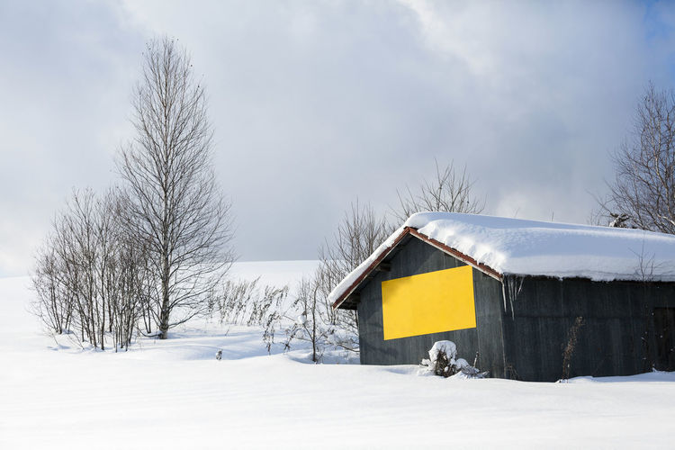Snow covered house on field against sky during winter