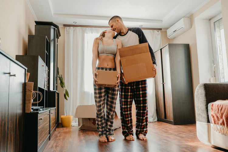Full length of couple holding boxes kissing while standing at home