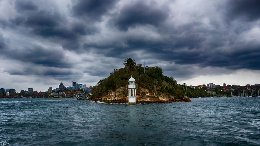 Lighthouse On Building By Sea Against Cloudy Sky