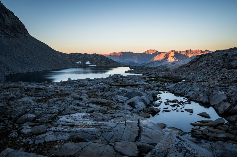 Scenic view of river amidst snowcapped mountains against sky during sunset