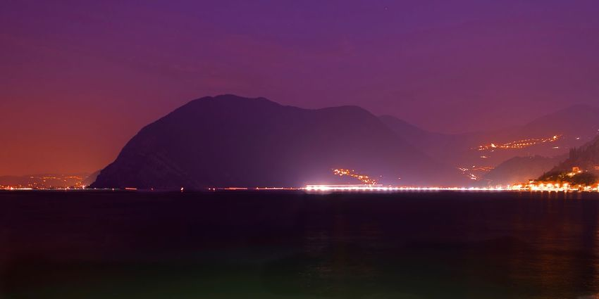 Floating On Water Floating Piers Iseo Lake Italy Brescia 2016 Christo Sulzano Water Mountain Illuminated Sky Night Nature Sea No People Beauty In Nature Scenics - Nature Tranquility Reflection Land Outdoors Travel Destinations Beach Mountain Range Tranquil Scene Sunset Purple Bay