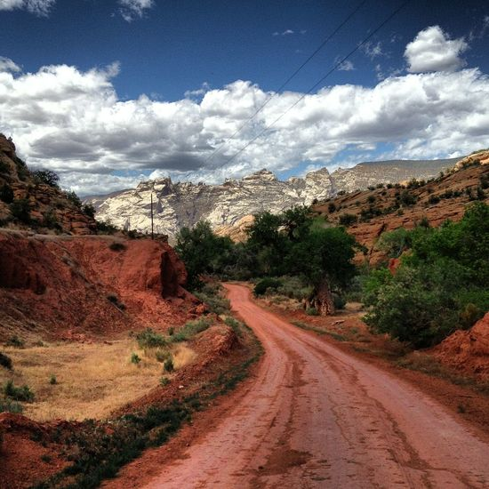 Red dirt road in Dinosaur National Park Utah Scenery Backroads Beauty In Nature Cloud - Sky Day Desolate Landscape Landscape Mountain Nature No People Outdoors Red Dirt Red Dirt Road Road Scenics Sky The Way Forward Tranquil Scene Tranquility Tree Winding Road