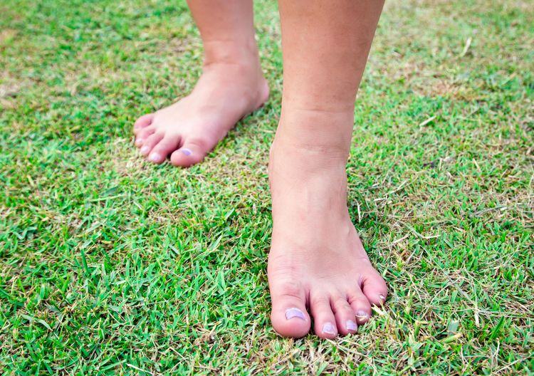 Low section of child legs on field